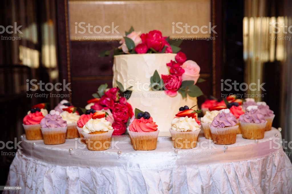 Candy bar, marshmallow on the table in a vase, a plate with candies in pink colour, macaroon, cake and cupcake on holiday, birthday or wedding decoration, decor vanilla, handmade. Concept of decoration royalty-free stock photo