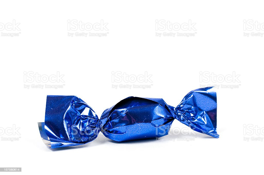 candy bonbon rolled into glittering blue aluminium foil stock photo