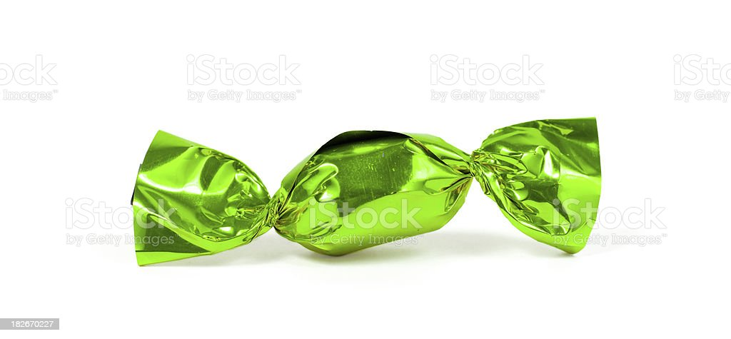candy bonbon rolled into glittering green aluminium foil stock photo