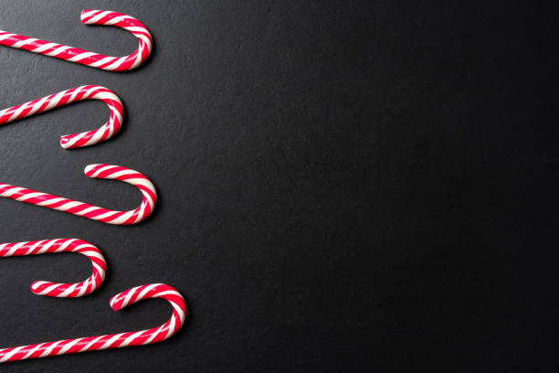 Candy cane over dark background Candy cane over dark background. Close up candy cane stock pictures, royalty-free photos & images