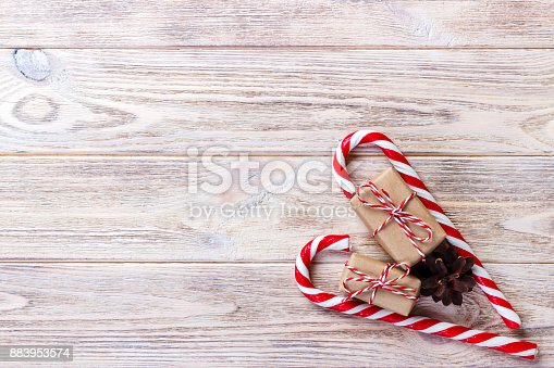 istock candy canes and christmas gift on brown wooden background 883953574