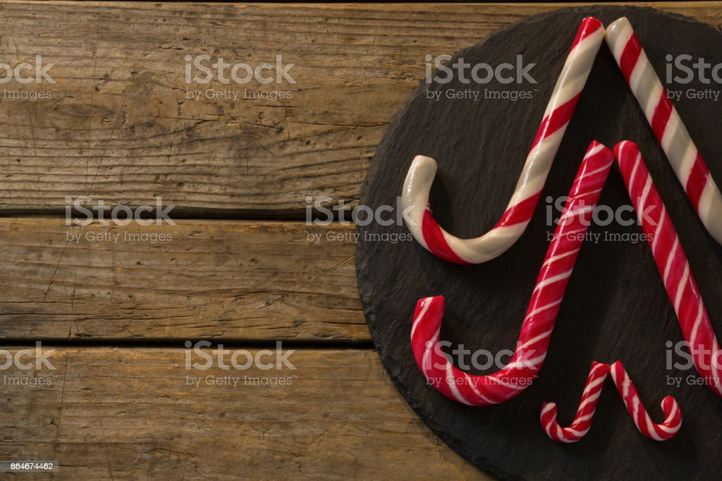 Candy canes arranged on wood stock photo