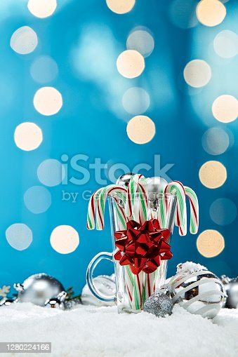 This is a photograph of Candy Canes in Glass surrounded by blue and white and Silver Christmas ornaments shot in the snow surrounded by glowing Christmas lights surrouned by evergreen palm tree branches. There are no people in the photograph