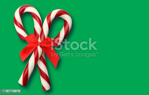 istock Candy Canes Isolated On Green Background 1182716978