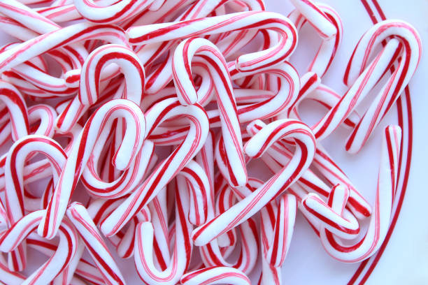 Candy canes Directly above view of a pile of candy canes on a red and white striped plate. candy cane stock pictures, royalty-free photos & images
