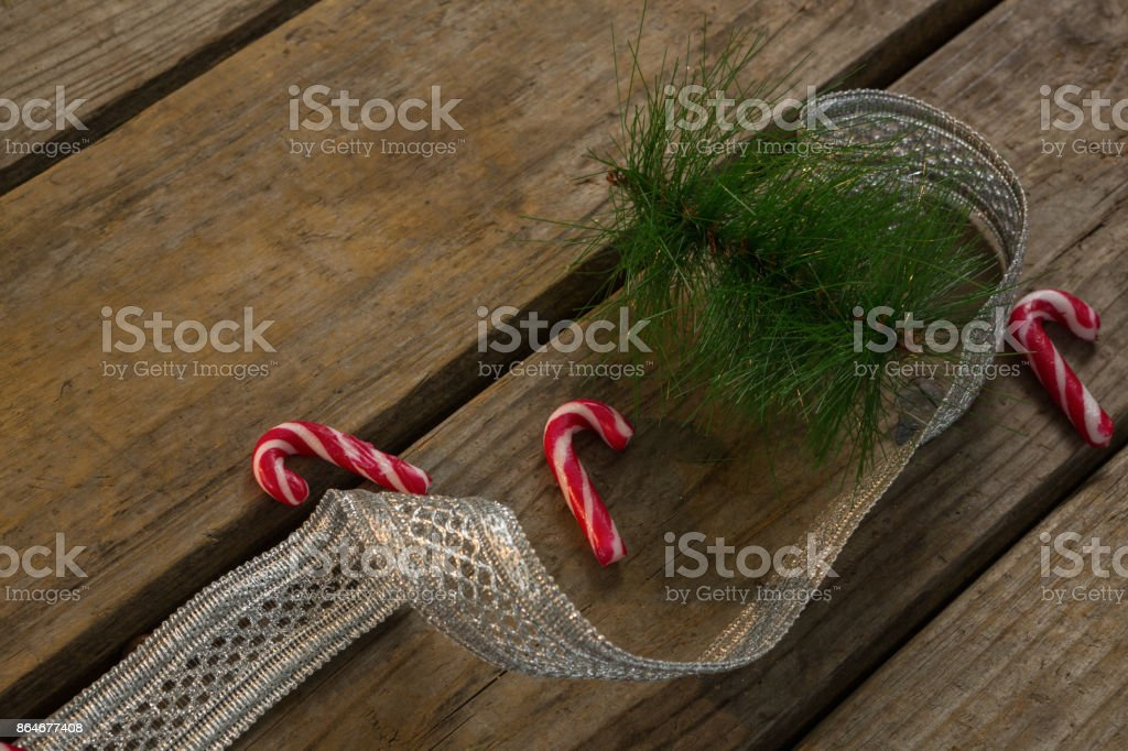 Candy canes with twigs and ribbon on table stock photo