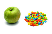 Candy. Green Apple with  multicolored sweets, dragees, chewing gum on a white background with focus stacking. Advertising label design element. Full depth of field.