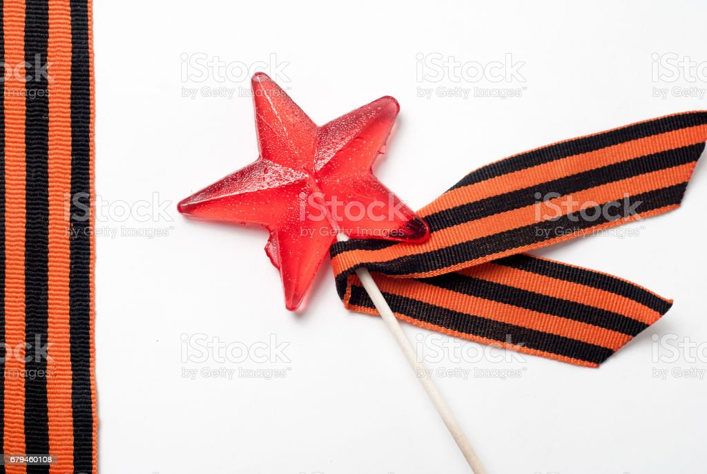 Candy in the shape of a star, a red candy on a stick, royalty-free stock photo