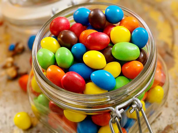 candy jar, chocolate covered peanuts - farbiges glas stock-fotos und bilder