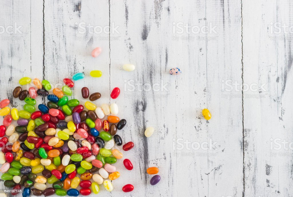 Candy jelly beans on bright wooden background stock photo