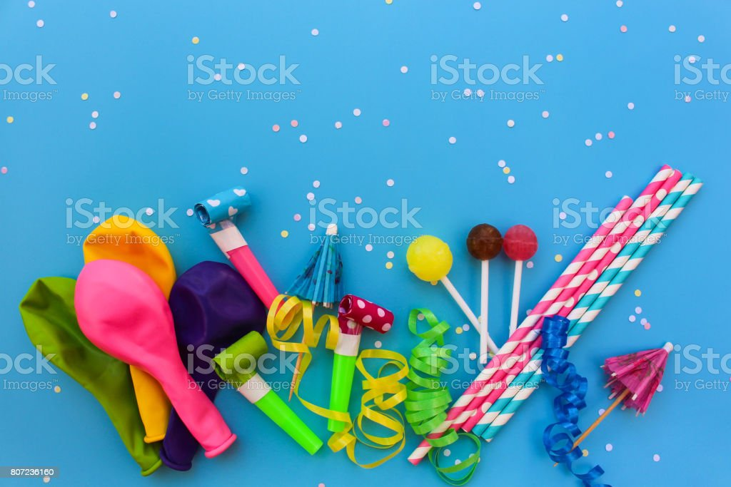 Candy, whistles, streamers, balloons on holiday table. Concept of children's birthday party. View top. stock photo