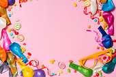Candy with colorful party items on pink background