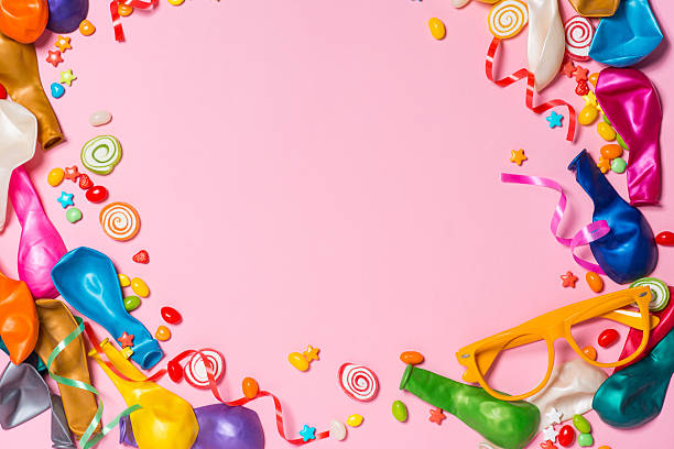 Candy with colorful party items on pink background - Photo