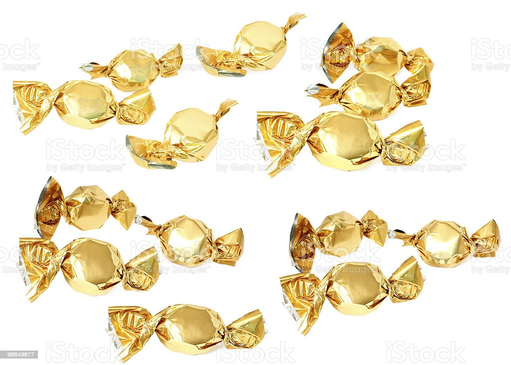 Candy with golden foil wrapper against white background stock photo