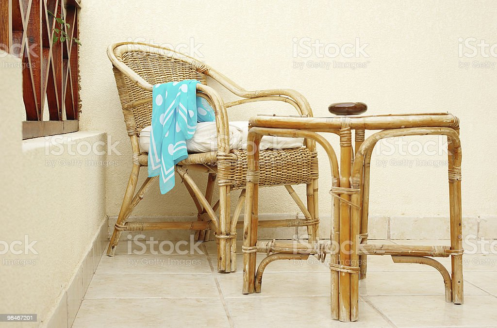 Cane chair and table with forgotten neckerchief royalty-free stock photo