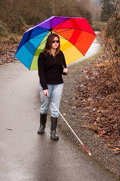Cane User with Bright Umbrella on Trail stock photo