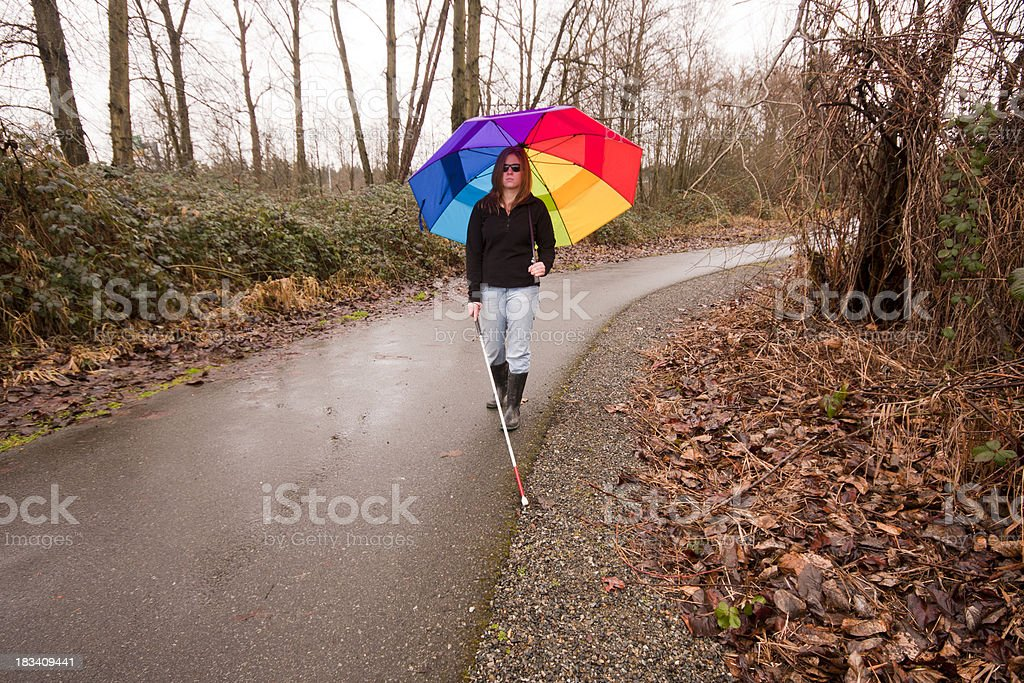 Cane User with Bright Umbrella on Trail stock photo