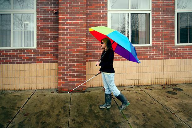 Cane User with Bright Umbrella stock photo