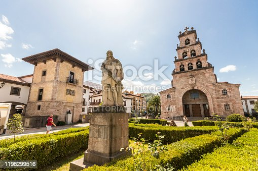 Cangas de Onis, Spain. The Iglesia de Santa Maria (St Mary's Church), with the monument to Don Pelayo (Pelagius of Asturias) in the foreground