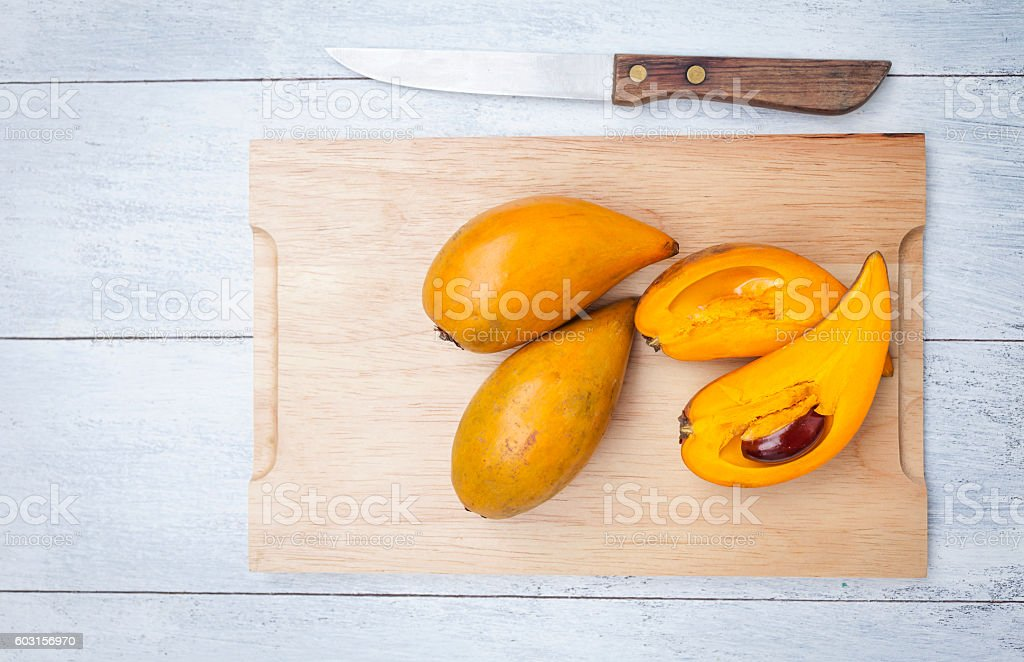 Canistel fruite on wooden cutting board stock photo
