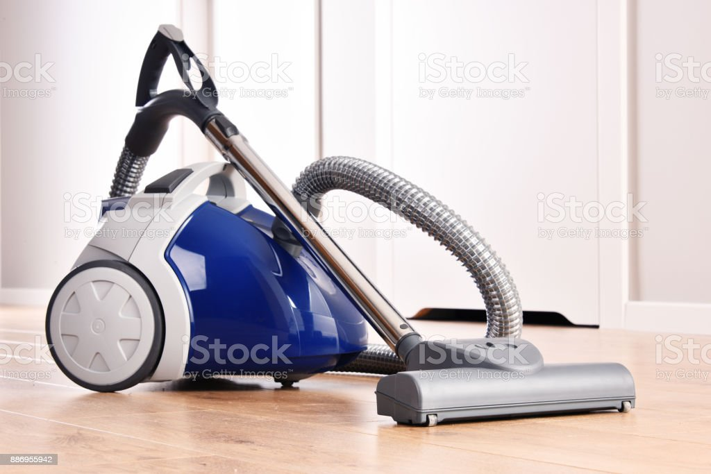 Canister vacuum cleaner for home use on the floor panels stock photo