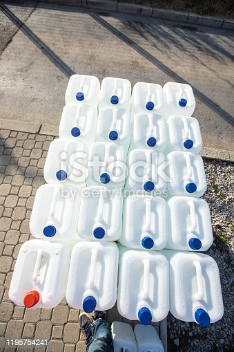 Heap of white plastic gallons of liquid on the street at gas station