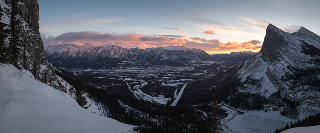 A panoramic sunrise view from the East End of Mount Rundle looking out over the town of Canmore within the Bow Valley of the Canadian Rockies.