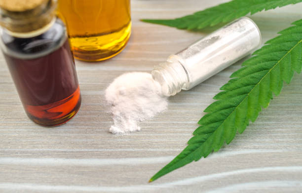 Cannabidiol CBD oils, and crystals isolate on wooden backdrop stock photo