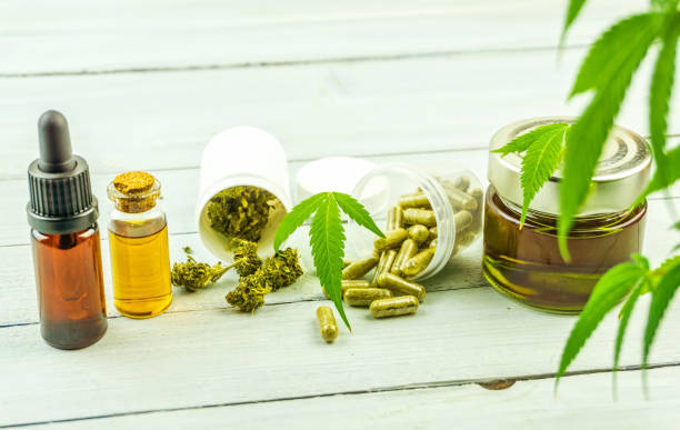 CBD cannabidiol oil glass bottles, pills flower buds and Cannabis leafs on bright wooden backdrop stock photo