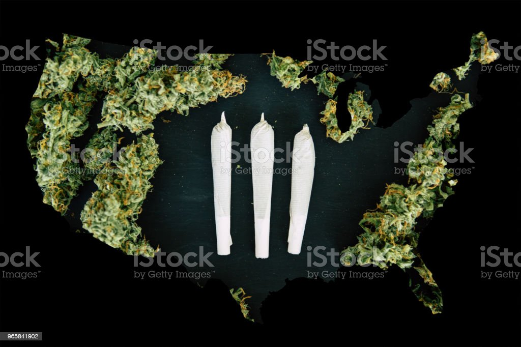 Cannabis Bud in the United State of America, Legal Marijuana in America. Grinder with crushed cannabis flowers and Joint and weed on the background of a black wooden table top view - Royalty-free Agriculture Stock Photo