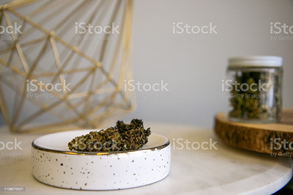 Cannabis Buds on Tray with Marijuana Shake in Glass Jar in Background - Cannabis Dispensary Products stock photo