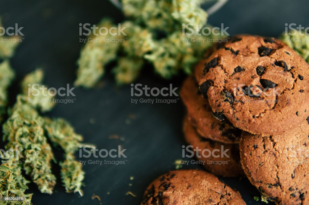 cannabis Cookies with and buds of marijuana on the table. Concept of cooking with cannabis herb. Treatment of medical marijuana for use in food, On a black background zbiór zdjęć royalty-free
