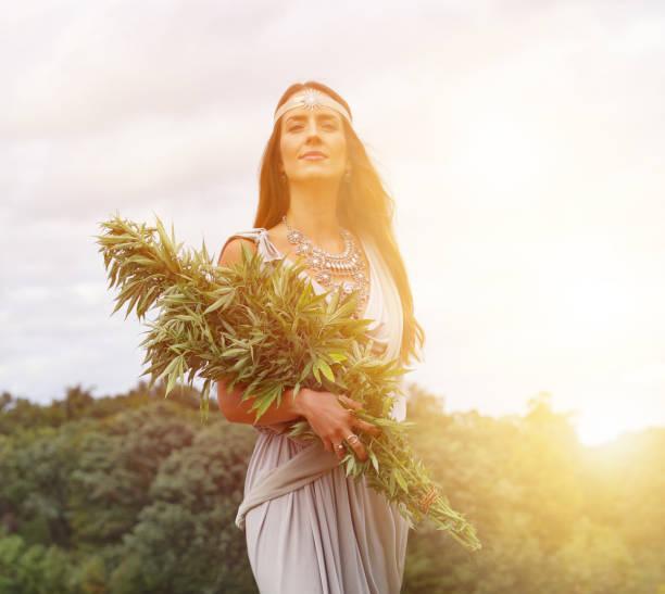Cannabis Göttin hält Bündel von Cannabispflanzen – Foto