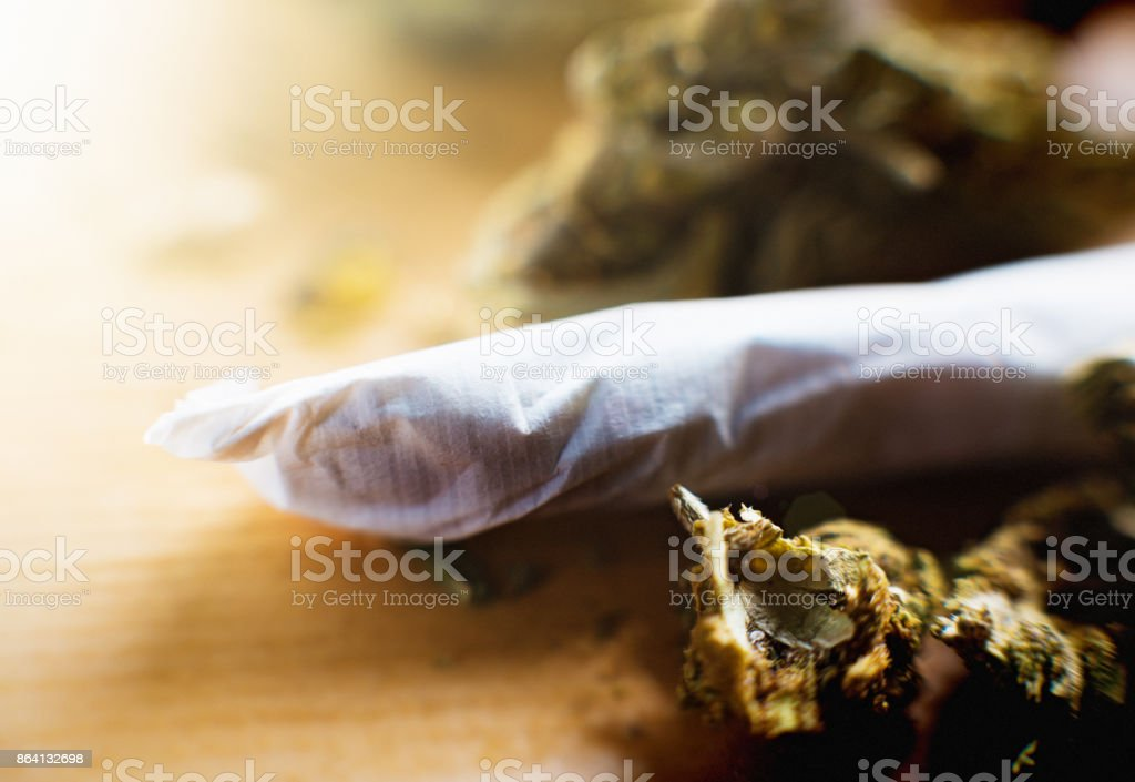 Cannabis joint with more loose marijuana in background royalty-free stock photo