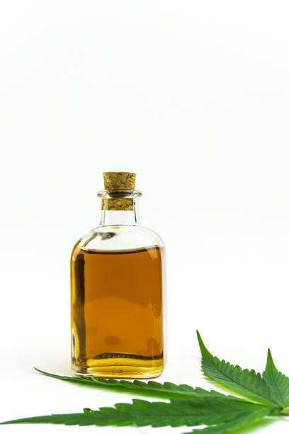 Cannabis leaf and Hemp CBD oil in jar isolated on white stock photo