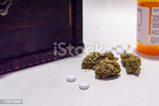 istock Cannabis marijuana flowers and prescription pain pills opioid narcotic. Alternative medicine. 1135216881