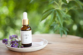 CBD Cannabis Oil (cannabidiol) bottle and dropper on small plate atop wooden surface. Fresh flowers on plate. Cannabis plant out of focus in background.