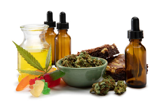 Cannabis oils and bud in a small bowl surrounded by sweet edibles stock photo