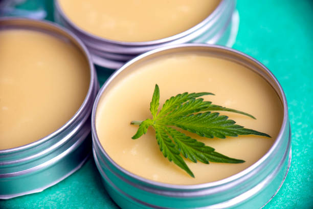 Cannabis salve with hemp and CBD oil on green background stock photo
