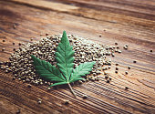 Cannabis seeds and leaf on a wooden background with copy space