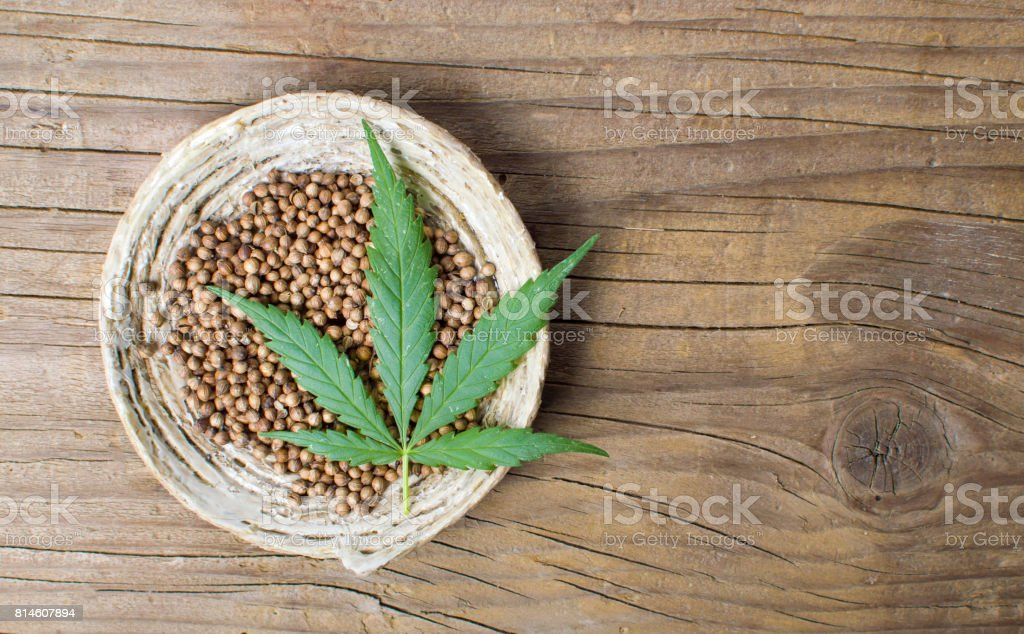 Cannabis seeds in a bowl on a wooden background stock photo