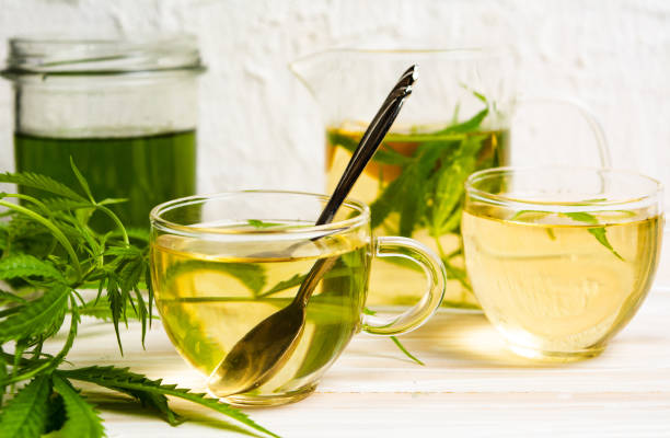 Cannabis tea with lemon and marijuana leaves Cannabis tea with lemon and marijuana leaves in a glass tea crop stock pictures, royalty-free photos & images