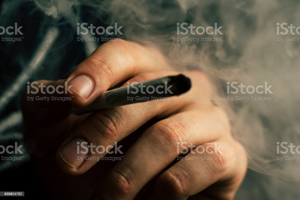 cannabis weed, a joint in his hands A man smokes . Smoke on a black background. Concepts of medical marijuana use and legalization of the cannabis. stock photo