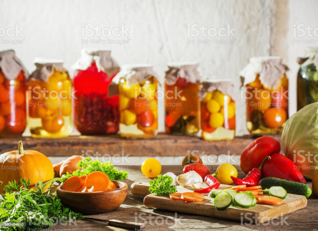 canned and fresh vegetables in jars stock photo