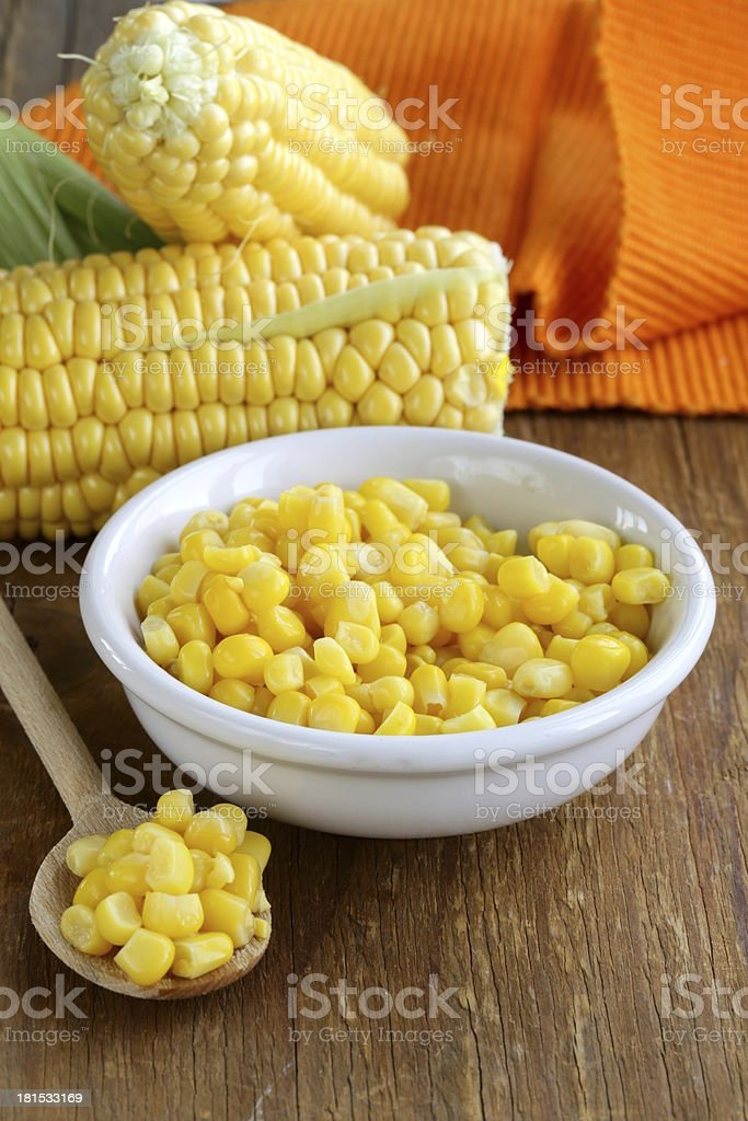 Canned corn in a bowl, and fresh cobs royalty-free stock photo