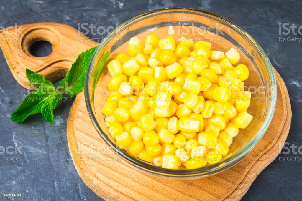Canned corn in a glass plate on a gray concrete background. stock photo