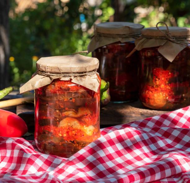 auberginenscheiben in pikanter gemüse-sauce im glas in dosen - peperoni stiche stock-fotos und bilder