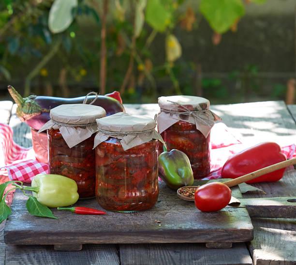 auberginenscheiben in würziger gemüsesauce in glasgefäßen gekonserviert - peperoni stiche stock-fotos und bilder
