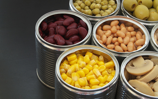 istock Canned food on black table background 1174438440