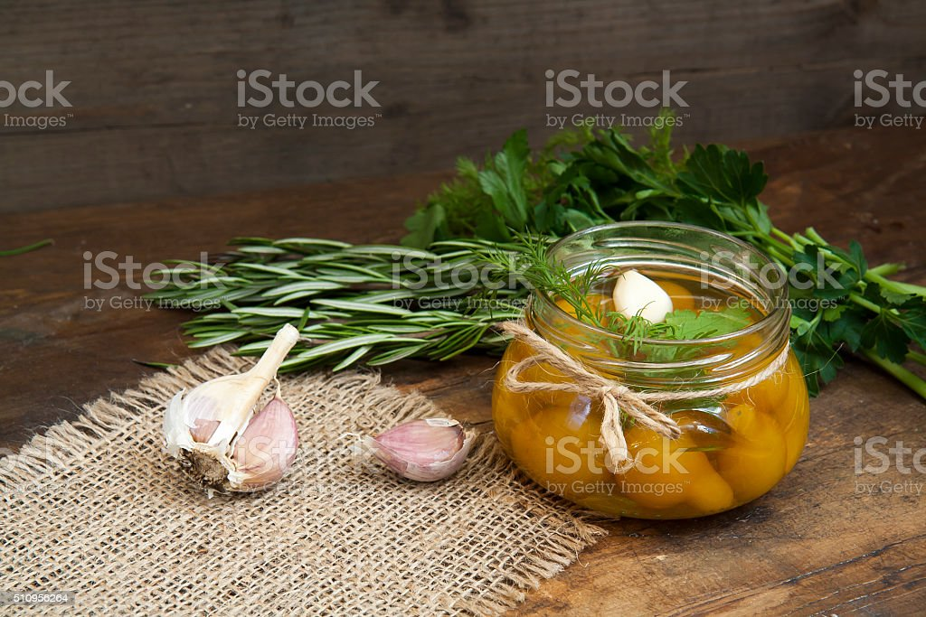 Canned marinated tomatoes in tomato juice on a wooden table royalty-free stock photo